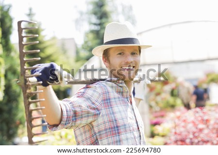 Portrait of smiling gardener carrying rake on shoulders at plant nursery - stock photo
