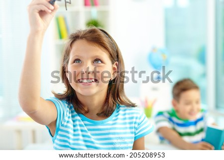 Portrait of smiling girl doing sums on transparent board with schoolmate on background
