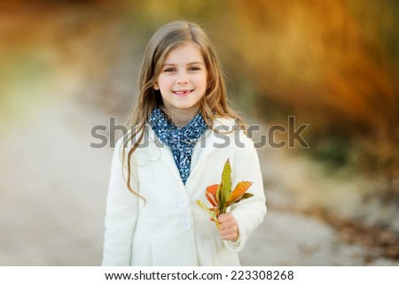 Portrait of smiling girl holding a bouguet of autumn leaves - stock photo