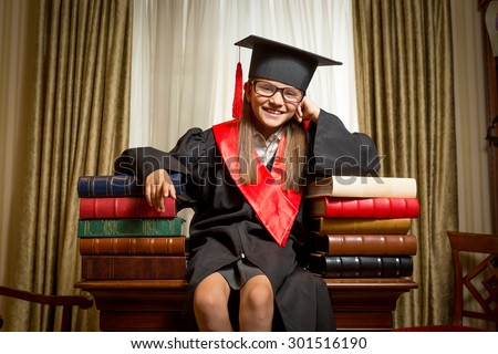 Portrait of smiling girl in graduation cap and gown sitting on table and leaning on books - stock photo