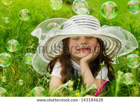 Portrait of smiling girl in hat laying on a grass with bubbles - stock photo