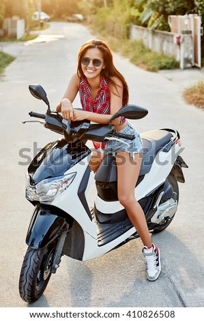 Portrait of smiling girl on scooter on the street  - stock photo