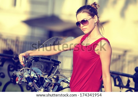 Portrait of smiling girl on scooter - Outdoor on street .Retro shot. Fashion colors. - stock photo
