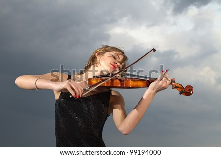 Portrait of smiling girl playing the violin - stock photo
