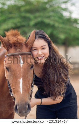 Portrait of smiling girl with a chestnut pony looking at the camera