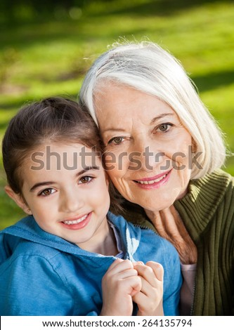 Portrait of smiling girl with grandmother at campsite - stock photo