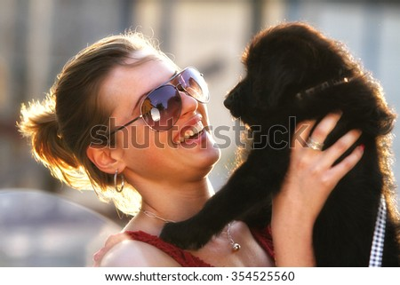 Portrait of smiling girl with puppy on scooter - Outdoor on street. Retro shot. Fashion art photo. - stock photo