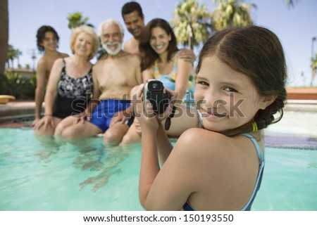 Portrait of smiling girl with video camera recording family in swimming pool - stock photo