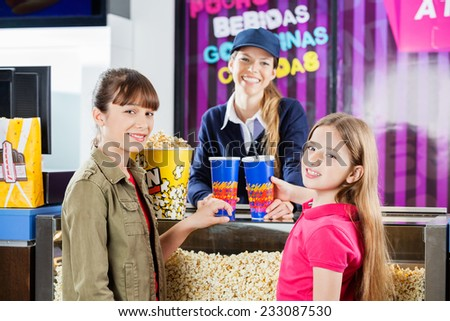 Portrait of smiling girls buying popcorn and drinks from female seller at cinema concession counter - stock photo