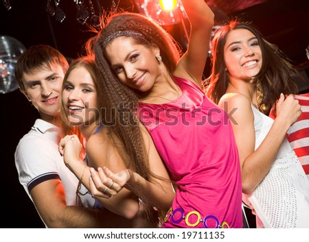 Portrait of smiling girls looking at camera on background of their friends - stock photo
