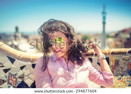 Portrait of smiling, gorgeous brunette girl with sunglasses on a windy day. Beautiful woman smiling and playing with hair on rooftop of building - stock photo