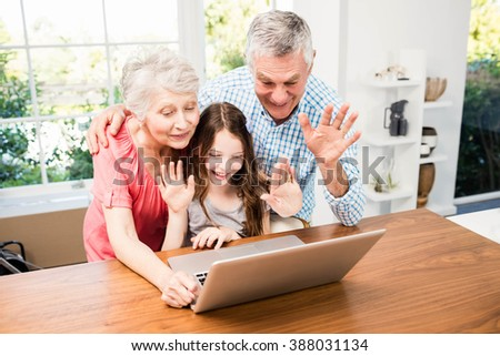Portrait of smiling grandparents and granddaughter using laptop at home