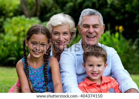 Portrait of smiling grandparents with grandchildren at yard - stock photo