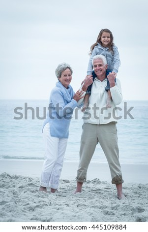Portrait of smiling grandparents with granddaughter at beach - stock photo