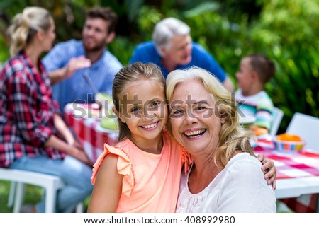 Portrait of smiling granny carrying girl during breakfast at yard - stock photo
