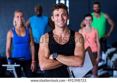 Portrait of smiling gym trainer holding clipboard while people standing in background