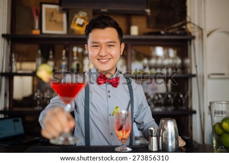 Portrait of smiling handsome bartender offering a cocktail
