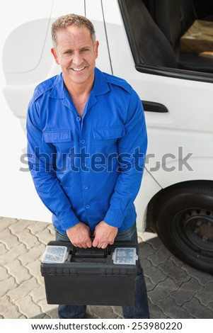 Portrait of smiling handyman carrying toolbox in front of his van