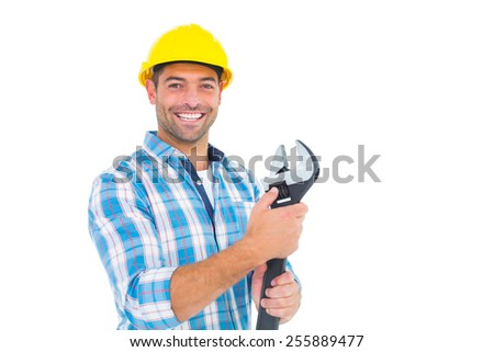Portrait of smiling handyman holding adjustable spanner on white background