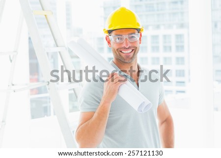 Portrait of smiling handyman holding rolled up blueprint in bright office - stock photo