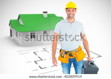 Portrait of smiling handyman holding toolbox against blue house behind an architectural plan - stock photo