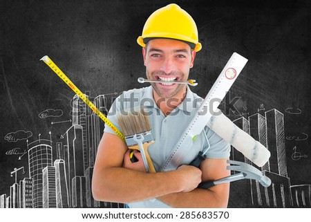 Portrait of smiling handyman holding various tools against hand drawn city plan - stock photo