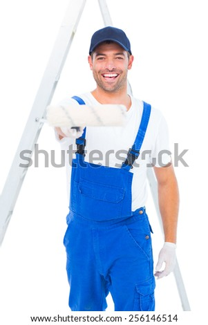 Portrait of smiling handyman using paint roller on white background