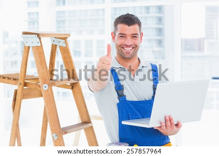 Portrait of smiling handyman with laptop gesturing thumbs up in bright office - stock photo