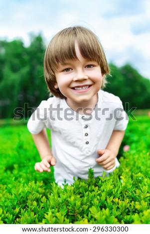 Portrait of smiling happy boy at green bush - stock photo