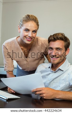 Portrait of smiling happy colleagues working in office - stock photo