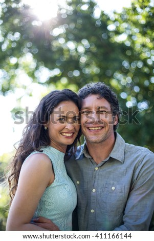 Portrait of smiling happy couple standing at park - stock photo