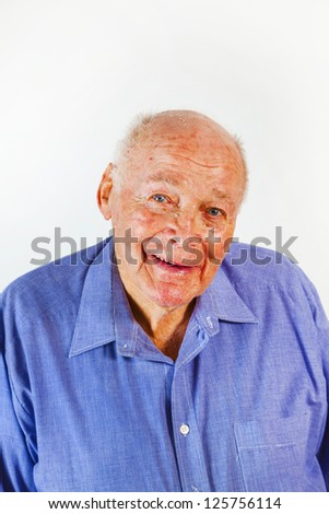 portrait of smiling happy elderly man in front of a white background