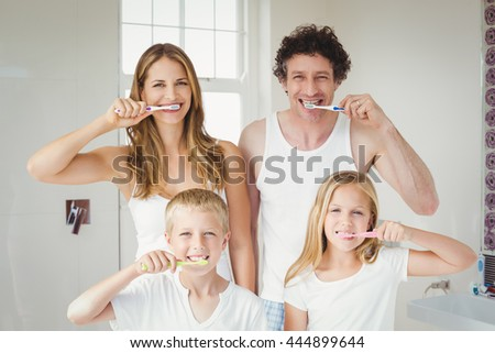 Portrait of smiling happy family brushing teeth at home - stock photo