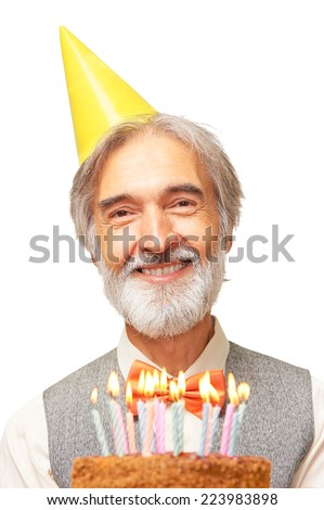 Portrait of smiling happy handsome caucasian elderly gentleman with gray beard and orange bowtie in the yellow festive hood holding birthday cake with candles in his hands isolated on white background - stock photo