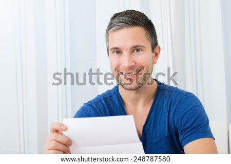 Portrait Of Smiling Happy Man Holding Letter - stock photo