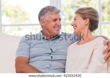 Portrait of smiling happy senior couple sitting at home. Senior couple relaxing at home and looking at each other with affection. Cheerful older couple enjoying after retirement. - stock photo