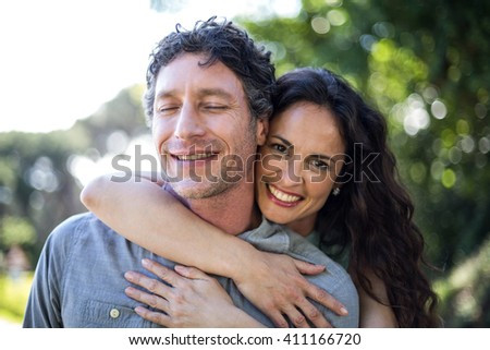 Portrait of smiling happy wife hugging husband at park - stock photo