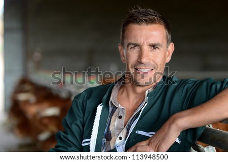 Portrait of smiling herdsman standing in barn - stock photo