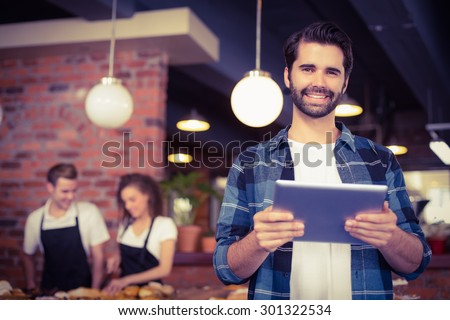 Portrait of smiling hipster using tablet in front of working barista at coffee shop - stock photo