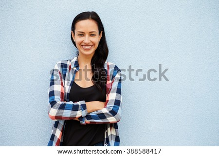 Portrait of smiling Hispanic woman against grey wall