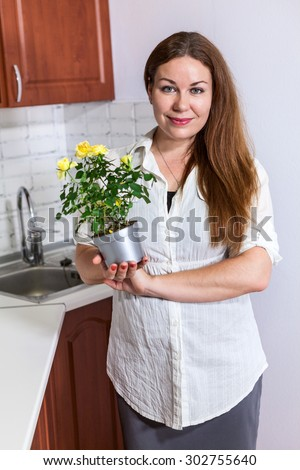 Portrait of smiling housewife holding yellow roses at pot in hands, domestic kitchen - stock photo