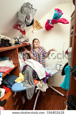 Portrait of smiling housewife in dressing room with clothes flying around