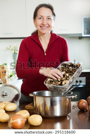Portrait of smiling housewife with dried mushrooms in home kitchen interior - stock photo