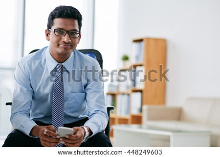 Portrait of smiling Indian business person with smartphone sitting in office