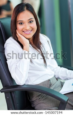 portrait of smiling indian business woman sitting in office - stock photo