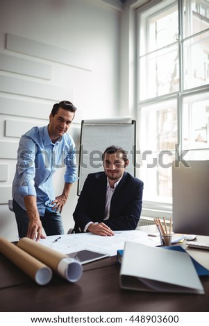 Portrait of smiling interior designer with male coworker working on blueprint in office - stock photo