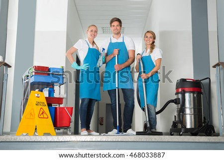 Portrait Of Smiling Janitors Holding Cleaning Equipments By Yellow Wet Caution Sign On Floor