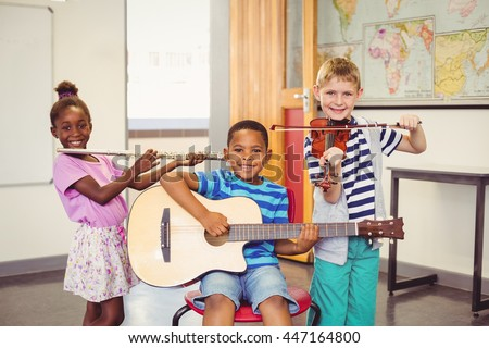 Portrait of smiling kids playing guitar, violin, flute in classroom at school - stock photo