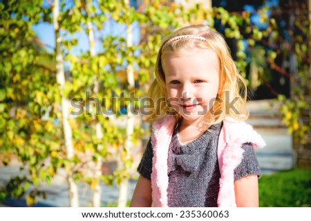portrait of smiling little blond girl in grey dress