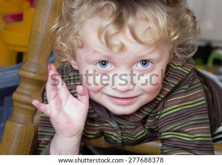 Portrait of  smiling  little boy under a chair - stock photo